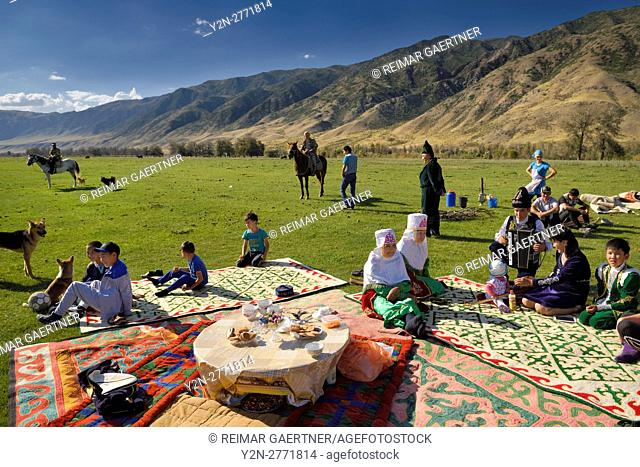 Saty townsfolk gathered for a picnic in pasture by the Chilik river and Kungey Alatau mountains Kazakhstan