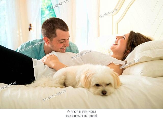 Pregnant woman and partner lying on bed with dog
