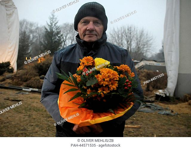 Shotfirer Horst Reinhardt holds a buquet of flowers in his hands as he stand next to the explosion crater in Oranienburg, Germany, 4 December 2013