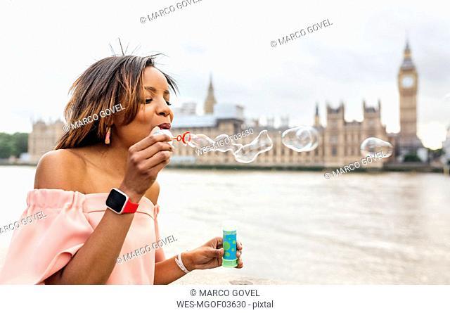 UK, London, woman making soap bubbles near Palace of Westminster