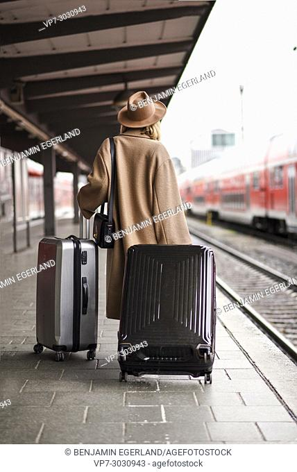 Fashion blogger Esra Eren aka @nachgestern travelling with trolley bags, waiting for train at platform at Munich central station, Germany