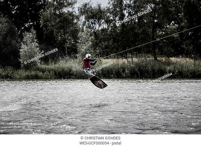 Germany, Garbsen, wakeboarder at Blue Lake jumping in the air