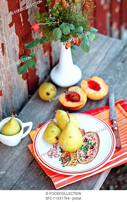 Peaches and pears on a wooden table in a garden