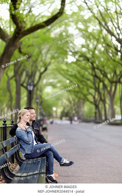Smiling couple sitting on bench in park