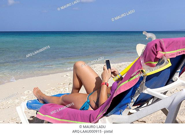 Girl Using Smartphone While Relaxing On Deck Chair On Beach In Cuba