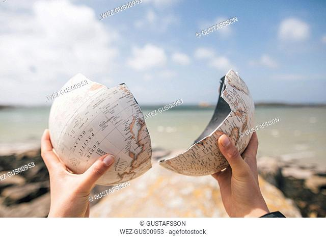 France, Brittany, Landeda, hands holding broken parts of a globe at the coast