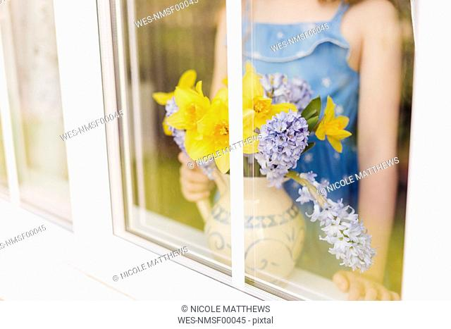 Flower vase of daffodils and hyacinths behind windowpane