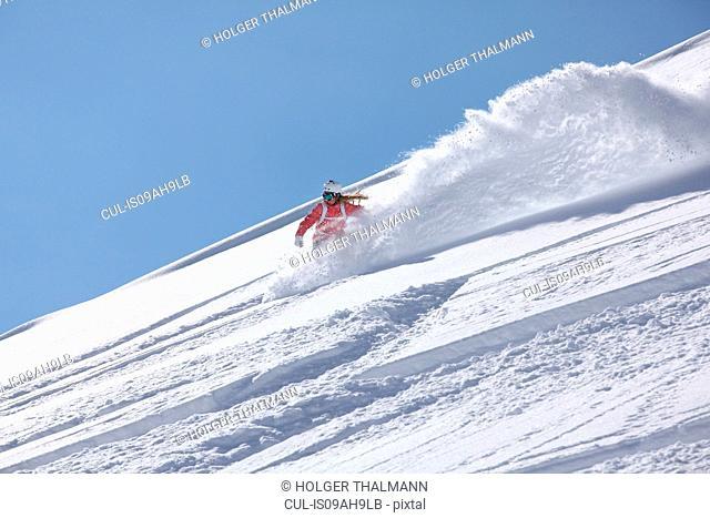 Young woman snowboarding down steep mountain, Hintertux, Tyrol, Austria