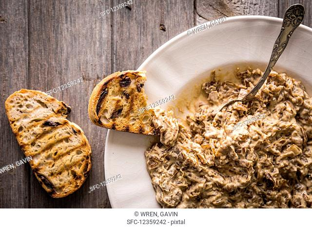 Caramelised onions with fish sauce and yoghurt in a white dish with spoon, alongside slices of charred toast
