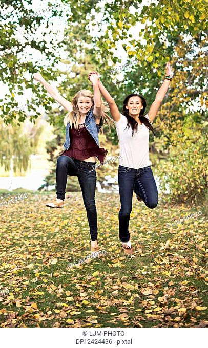 Two girlfriends leaping for joy in a park in autumn; Edmonton, Alberta, Canada