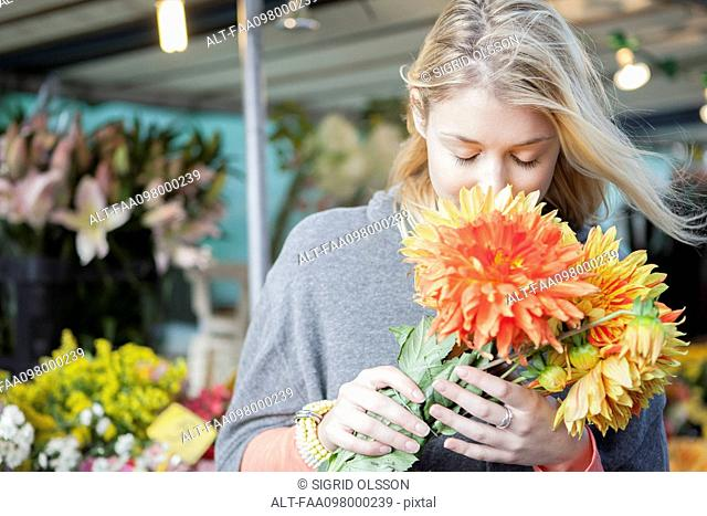 Young woman appreciating flower bouquet fragrance