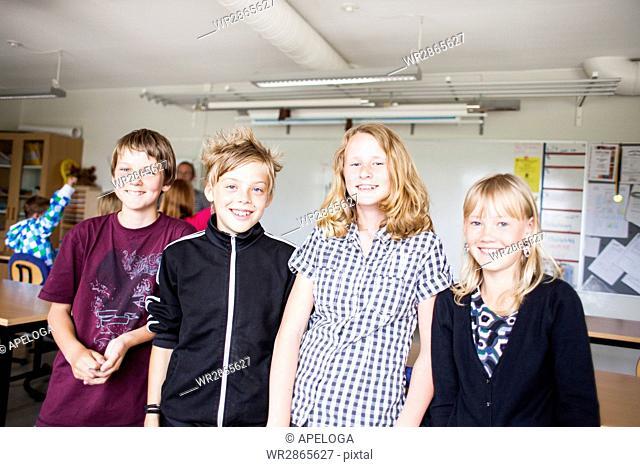 Portrait of happy school students standing in classroom