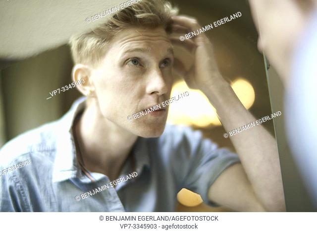 young man checking his appearance in mirror