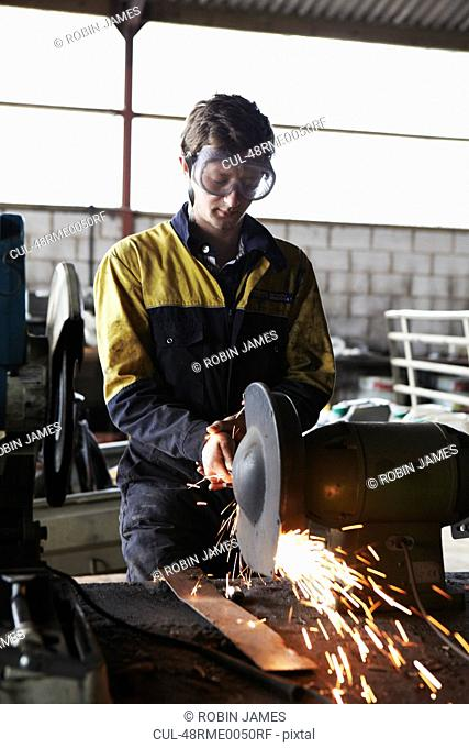 Metal worker using grinder in shop