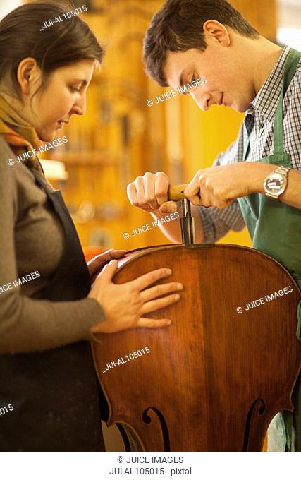 Violin makers working on a cello in workshop