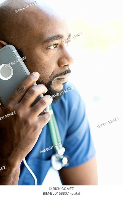 Black nurse talking on cell phone near window