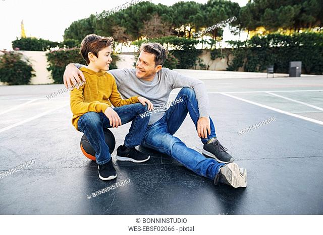 Father embracing son on basketball outdoor court