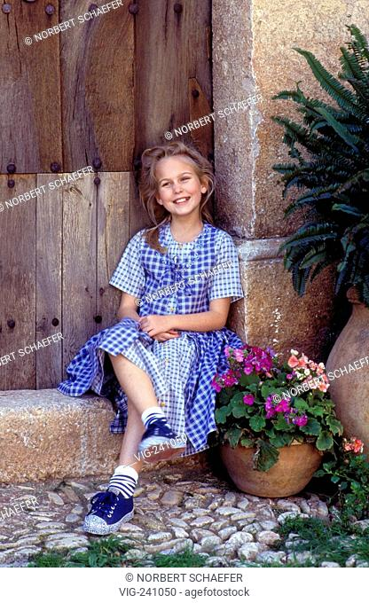 portrait, blond girl , 10 years, wearing white-blue checked dress and blue canvas sits laughing on a stonen step in front of an old wooden door  - GERMANY