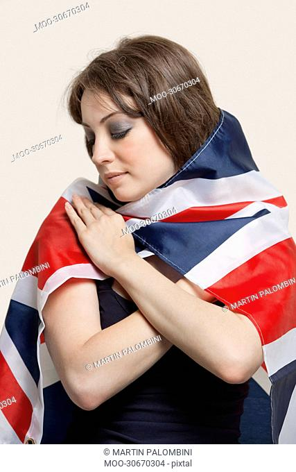 Young woman wrapped in British Flag over gray background