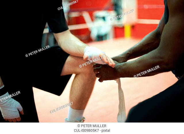 Coach helping boxer bandage hands before putting on gloves, mid section
