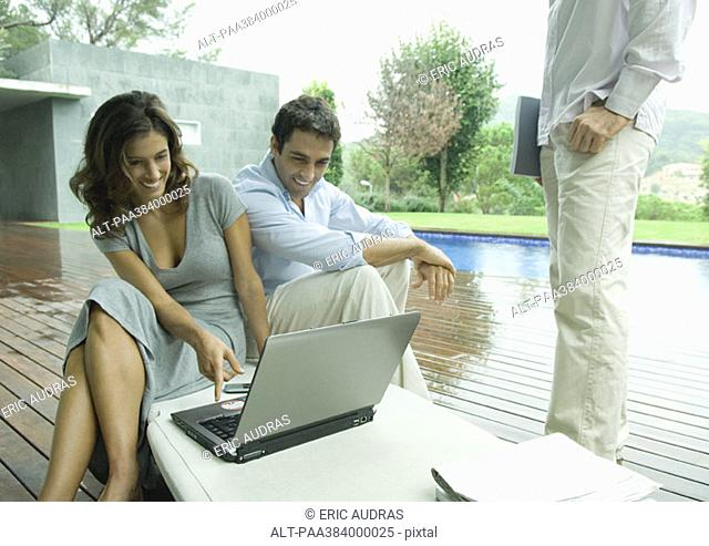 Casually dressed young executives working near edge of pool