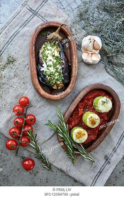 Two baked vegetable dishes in rustic serving trays (top view)