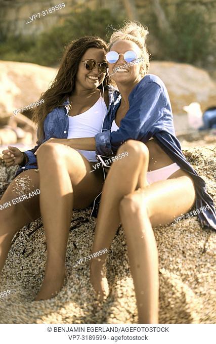 Two women lying in sand at beach, Chersonissos, Crete, Greece