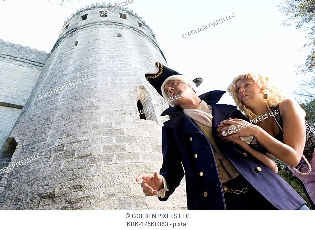 Low angle view of a navy officer and a princess sneaking around a castle wall and turrets