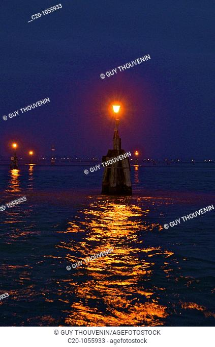 the Laguna at night ,'bricole ' or wooden posts with their lights , that mark out the navigable zones in the laguna of Venice ,Italy