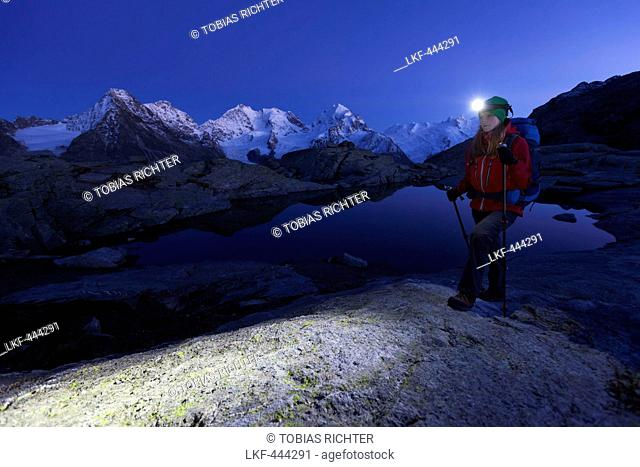 Female hiker with headlamp passing a mountain lake above the Roseg valley, Piz Morteratsch, Piz Bernina and Piz Roseg in background, Engadin, Canton of Grisons