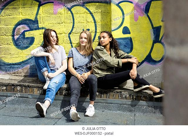 Three teenage girls relaxing on roof top in front of graffiti