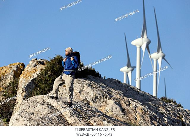 Spain, Andalusia, Tarifa, man on a hiking trip standing on rock with wind turbines in background