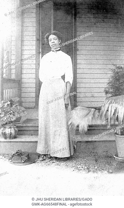 Full-length portrait of African American woman standing in front of a porch, wearing a white dress, with her hat on the ground, potted plants by her side