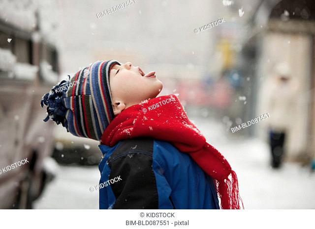 Caucasian boy catching snowflakes on tongue