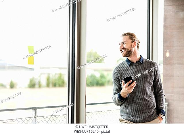 Laughing young businessman with cell phone looking out of window