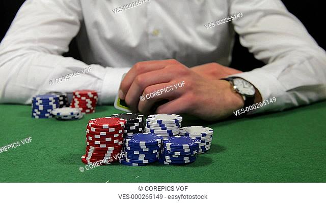 Poker player winning the pot with a pair of tens