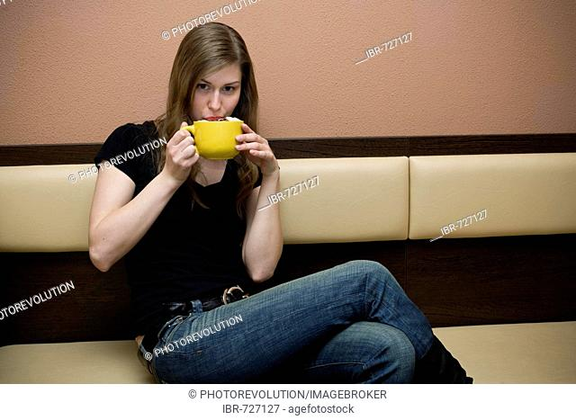 Young woman drinking a cup of latte in a bar