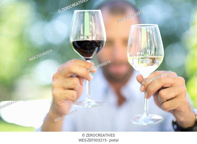 Man comparing white wine and red wine on a wine tasting session