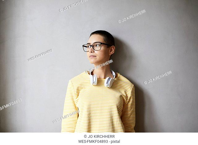 Portrait of short-haired young woman wearing glasses and headphones