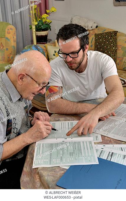 Grandson helping his grandfather by making tax declaration