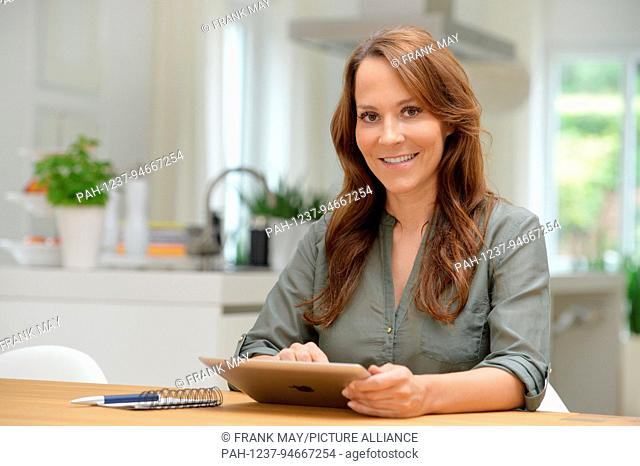 A young woman is doing some online shopping at home (model released) , Germany, city of Seesen, 11. September 2017. Photo: Frank May | usage worldwide