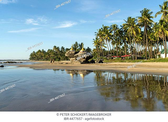 Golden pagodas on rocks at palm beach, Ngwe Saung, Myanmar