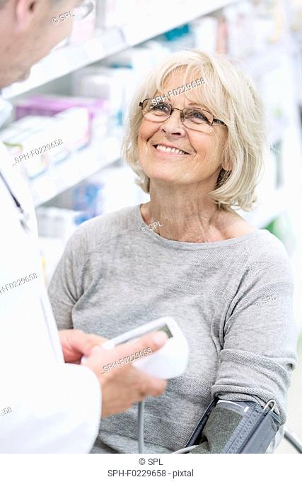 Pharmacist checking blood pressure