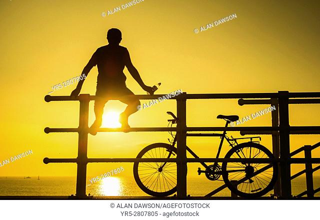A mountain biker on sea wall watching the sun rise over the North sea at Seaton Carew on the north east coast of England, United Kingdom. Europe,