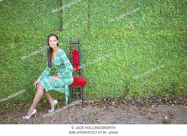Young woman sitting in front of hedge