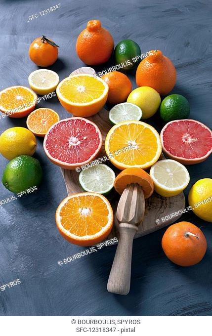 Various halved citrus fruits on a board with a wooden citrus reamer