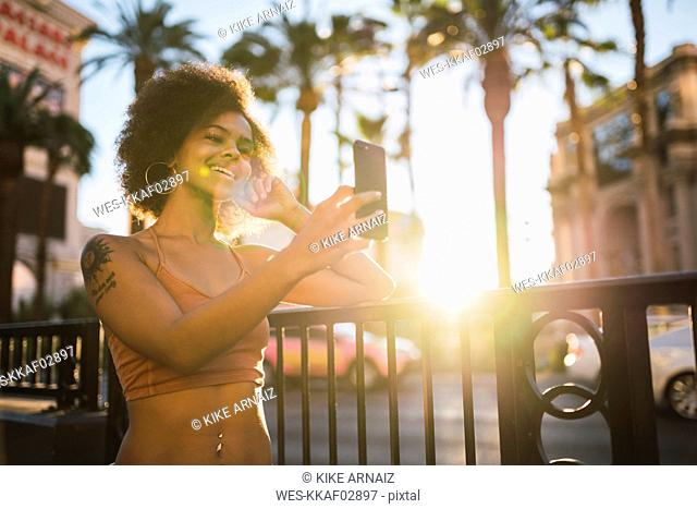 USA, Nevada, Las Vegas, happy young woman taking a selfie in the city