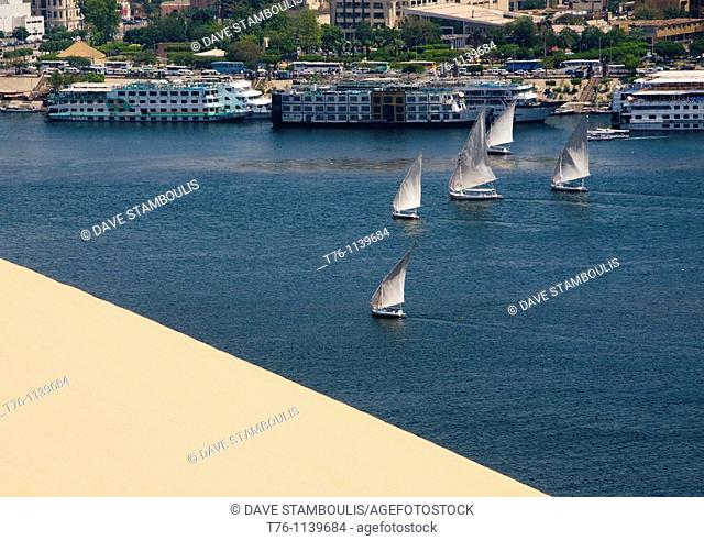 feluccas and cruise ships sailing in front of a sand dune on the Nile River in Aswan Egypt