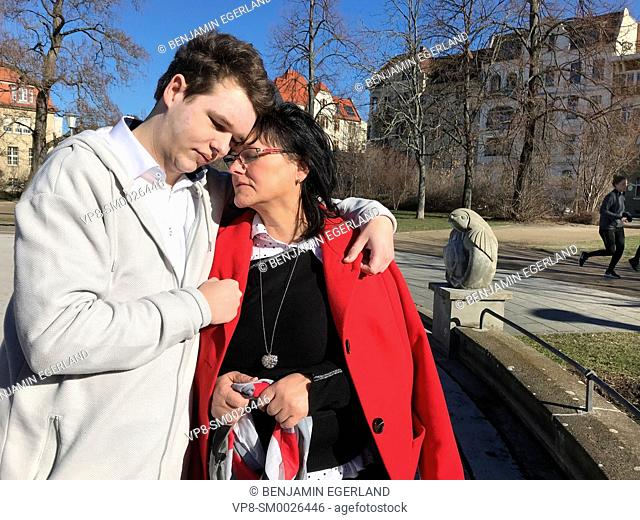 mother and son with vitiligo, skin depigmentation, skin disease, embracing together outdoors in city, Cottbus, Brandenburg, Germany