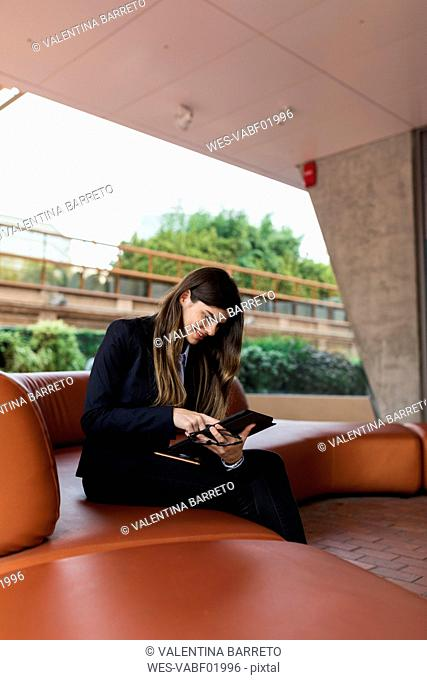 Smiling young businesswoman sitting in a lounge using tablet